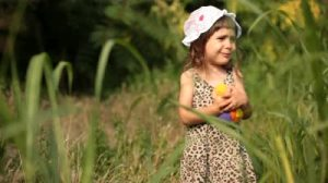 stock-footage-little-baby-girl-lost-in-forest-carries-ball-and-notebook